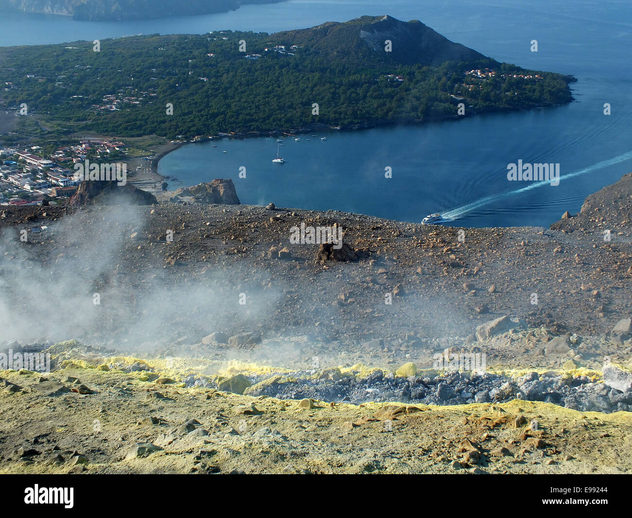 The sulfur-yellow peaks of the Gran craters with its fumaroles rises menacingly above the harbor of Porto Levante Stock Photo