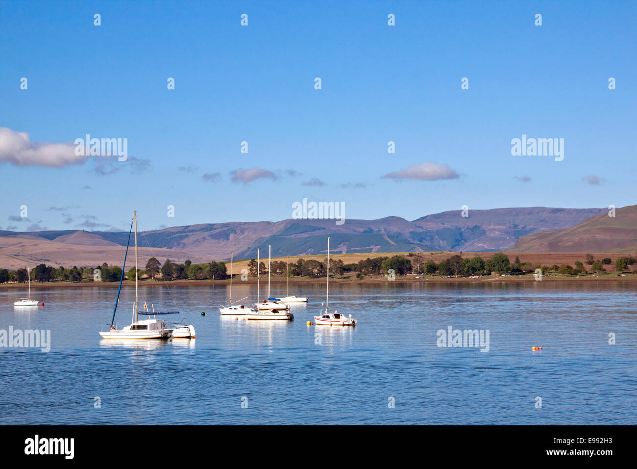Low-lying clouds on the mountains overlooking yacht anchored in Midmar dam in the  Midlands of Natal in South Africa Stock Photo