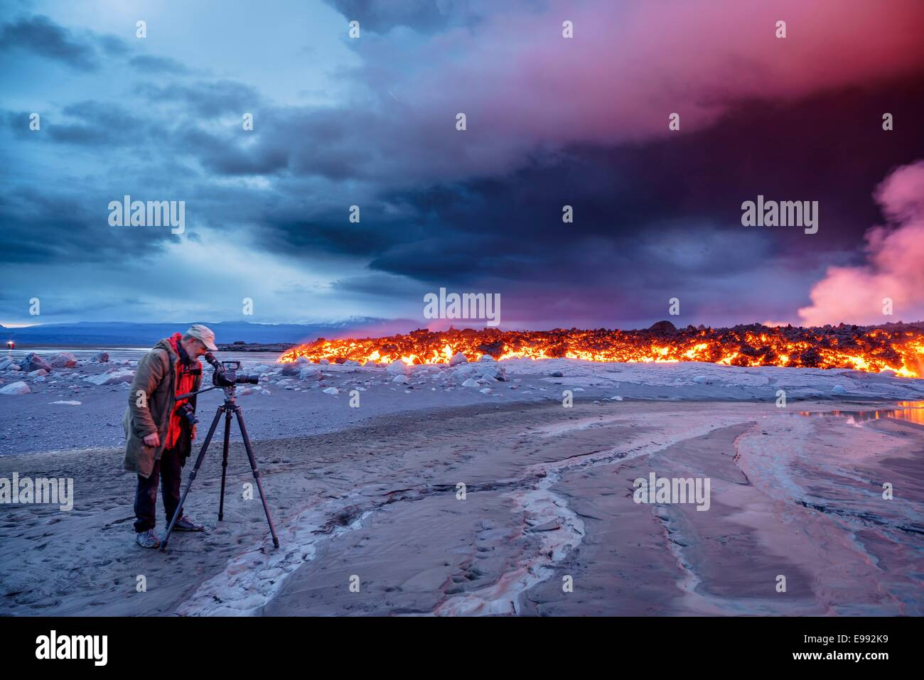 Photographer filming the volcano eruption at the Holuhraun Fissure, near the Bardarbunga Volcano, Iceland. - Stock Image