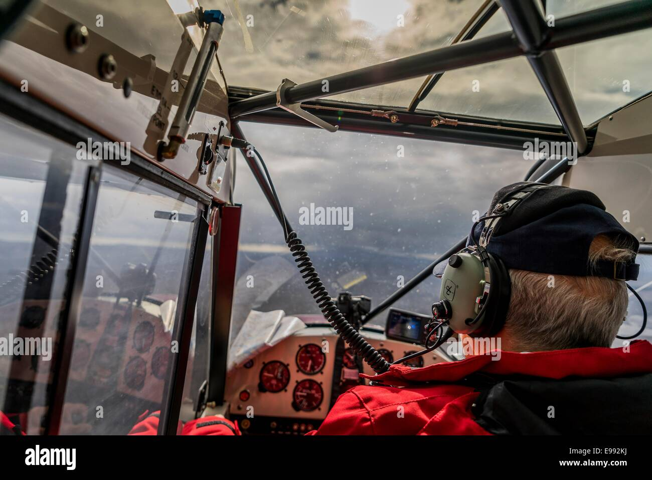 Pilot flying a Super Cub airplane by the Holuhraun Fissure Euruption, Iceland. - Stock Image