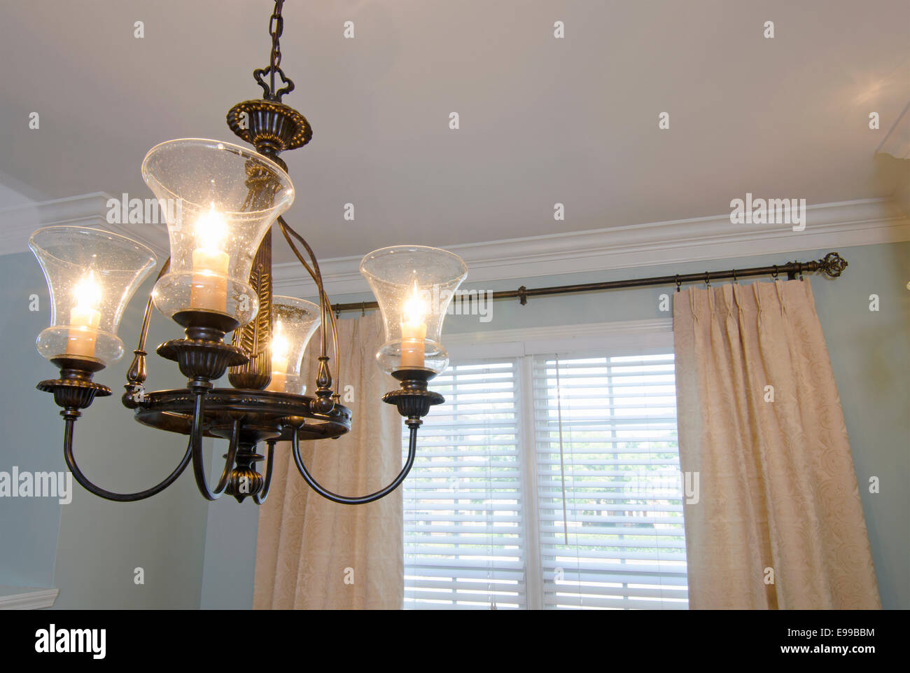 Light Fixture: A traditional style light fixture with hand-blown globes hanging in a dining room. - Stock Image