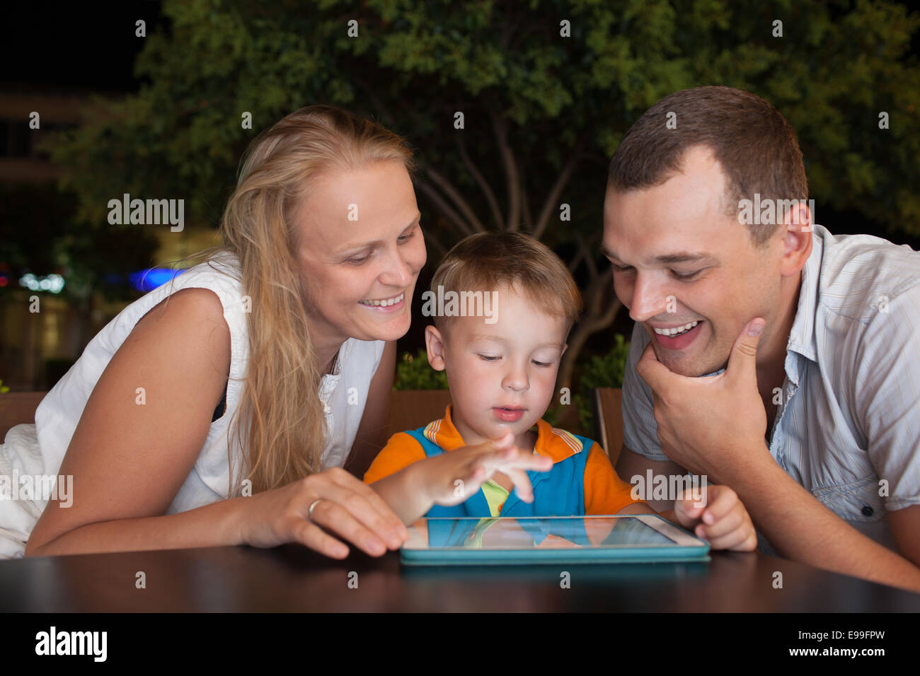 Family of three with pad in outdoor cafe - Stock Image