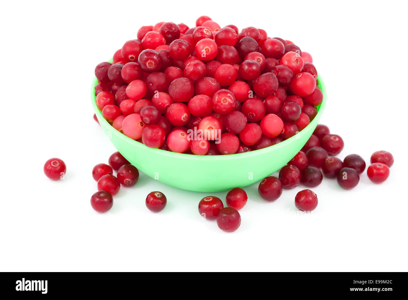 frozen cranberry in green bowl on white - Stock Image