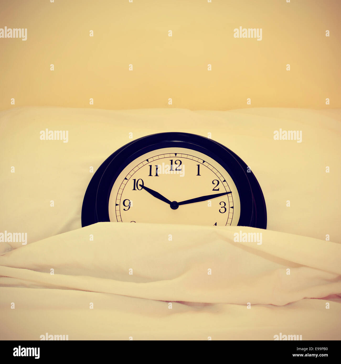 picture of a clock inside a bed, with a retro effect - Stock Image