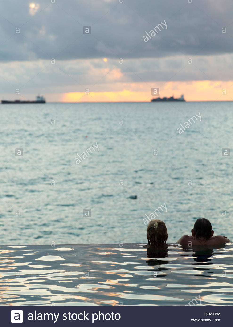 Silhouetted head against infinity edge pool Stock Photo