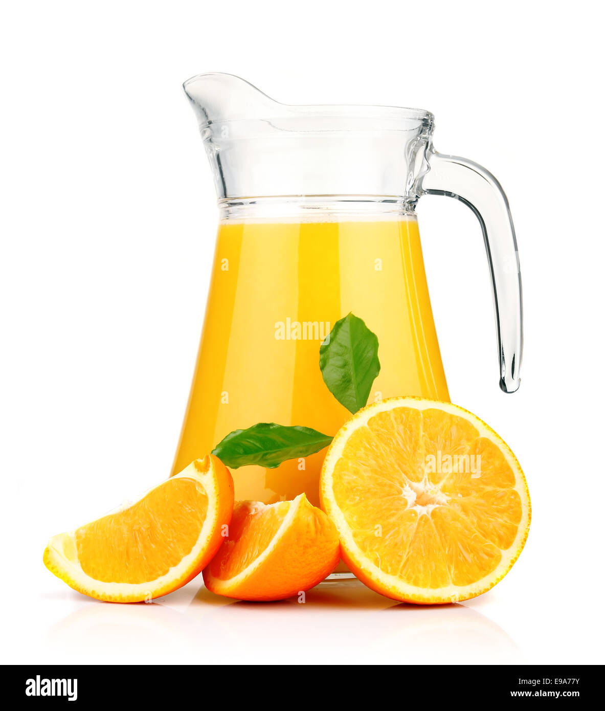 Orange juice in pitcher and oranges. - Stock Image