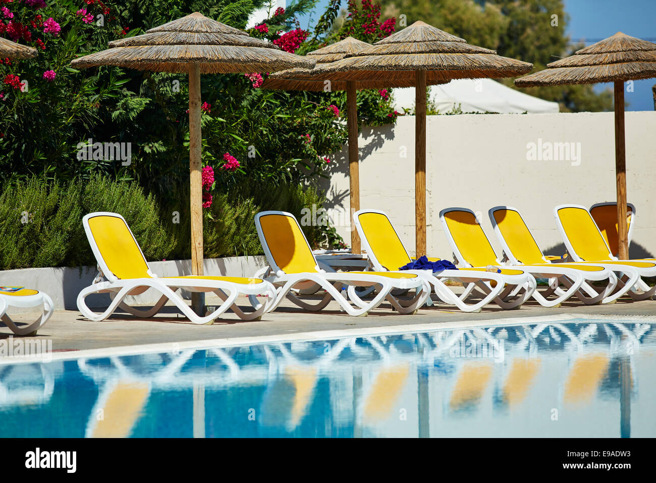 Empty sun loungers around swimming pool - Stock Image
