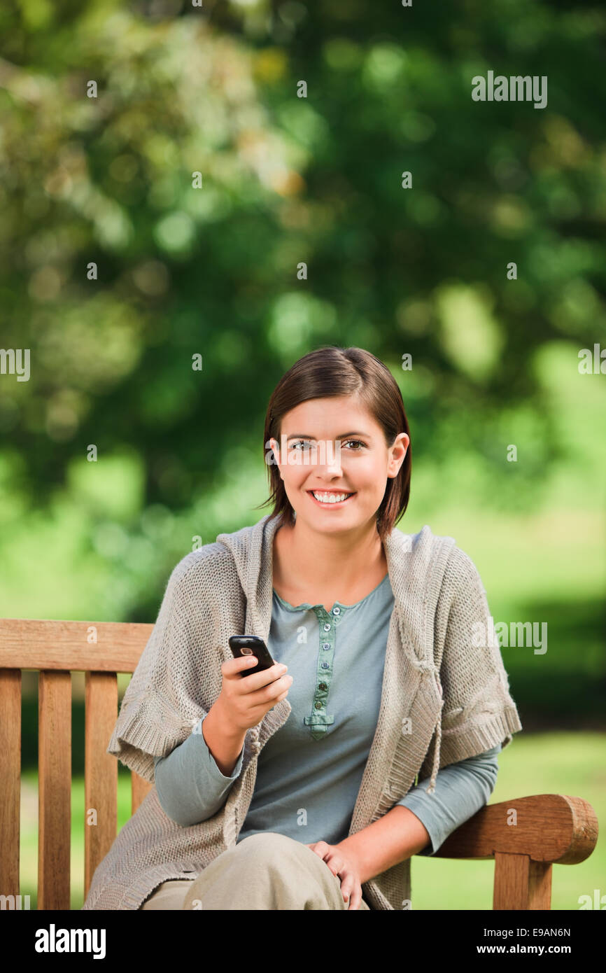Woman phoning on the bench - Stock Image