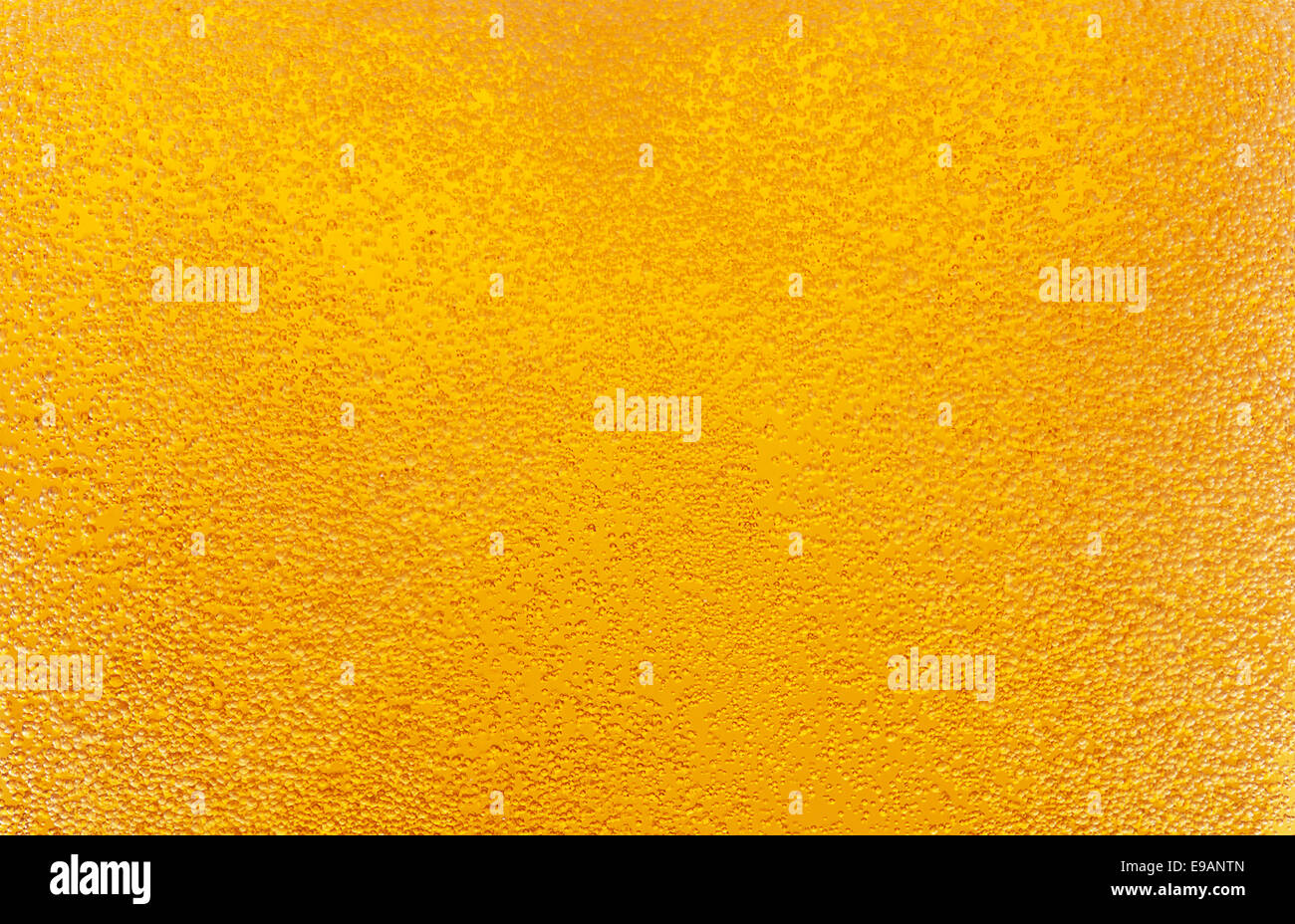 Close-up of golden bubbles in beer. - Stock Image