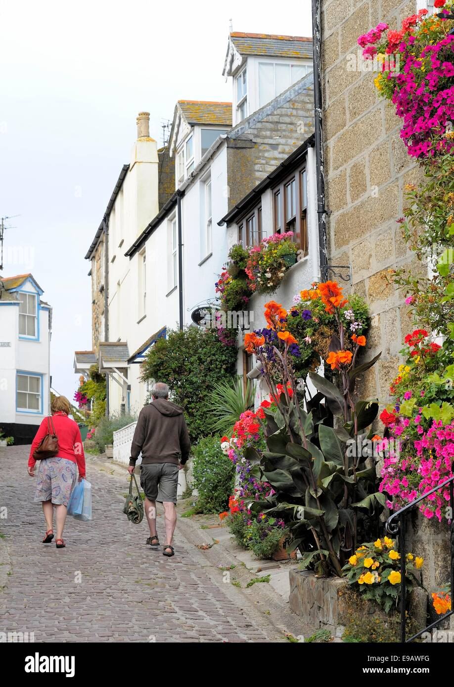 A man and a woman carrying bags walking up love lane St Ives Cornwall England uk - Stock Image