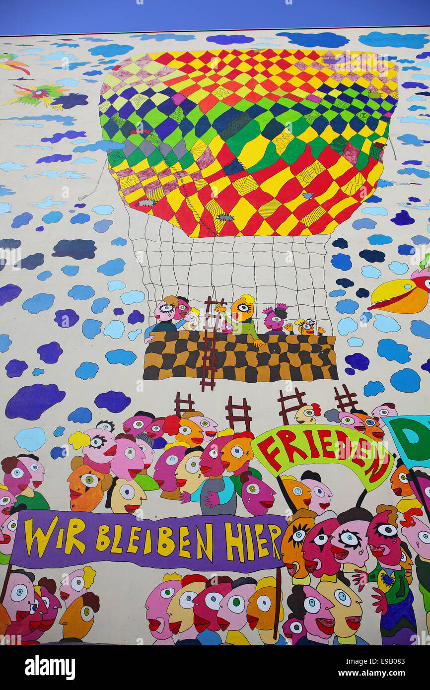 Colourful mural with the words 'Frieden' and 'Wir bleiben hier', German for 'peace' and - Stock Image