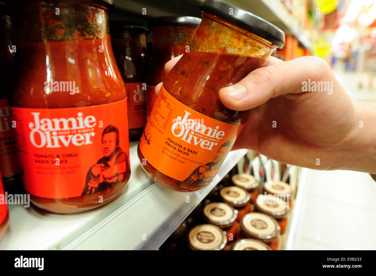 taking Jamie oliver product from shelf (Newscast)(Model Released) - Stock Image
