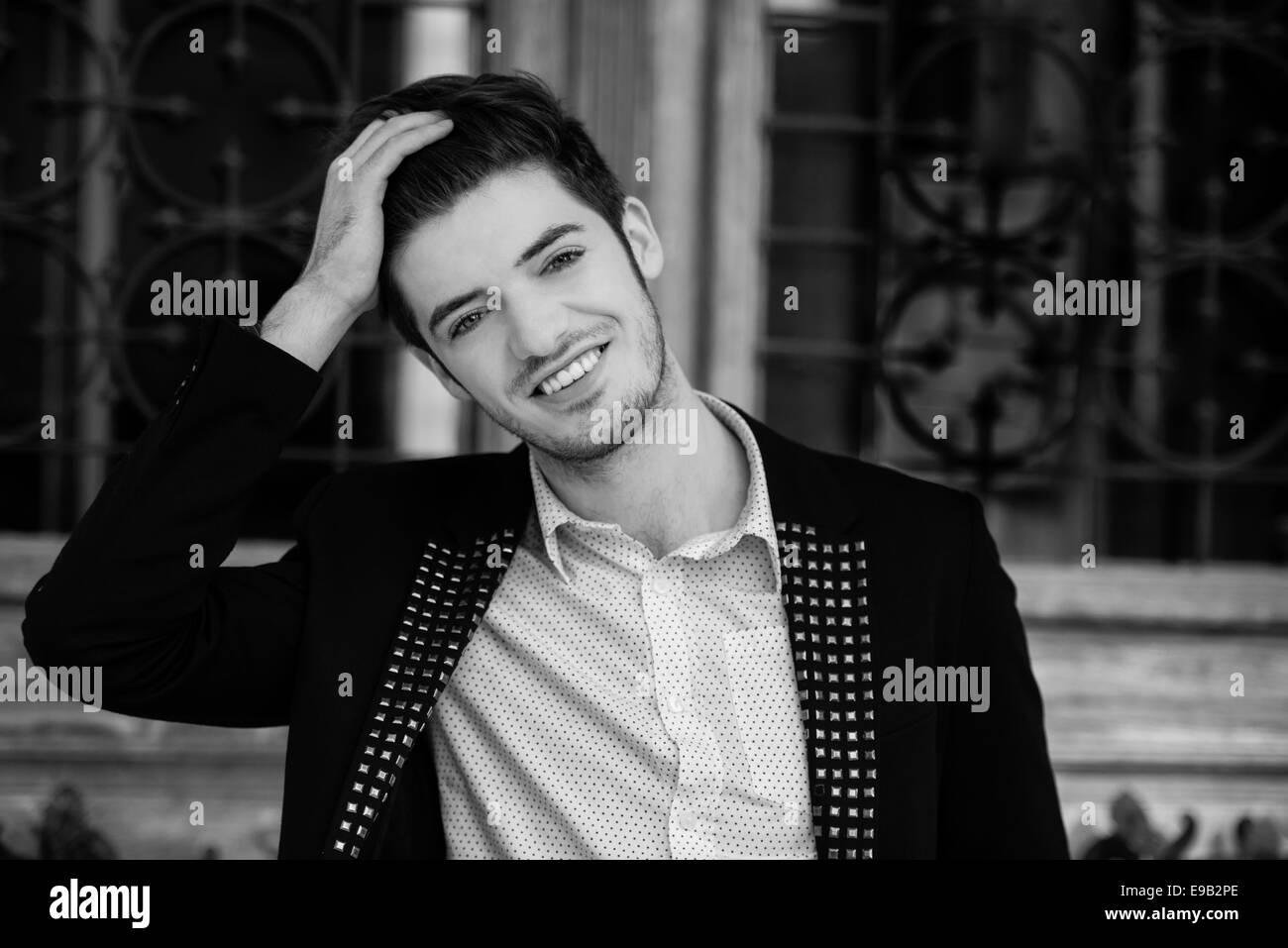 Black and white portrait of an attractive young man smiling - Stock Image