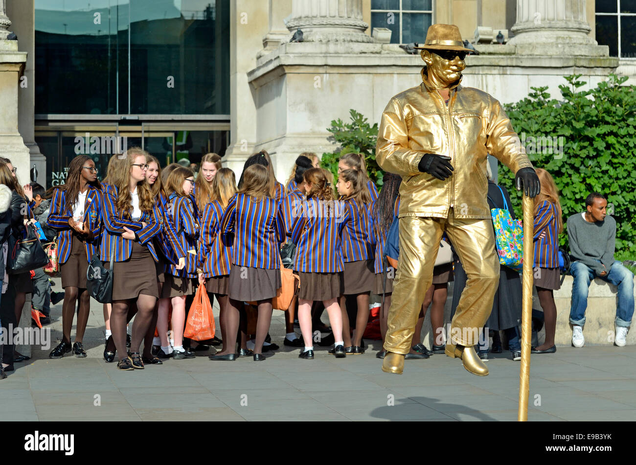 London, England, UK. 'Floating' human statue and a group of schoolgirls on a trip in Trafalgar Square - Stock Image