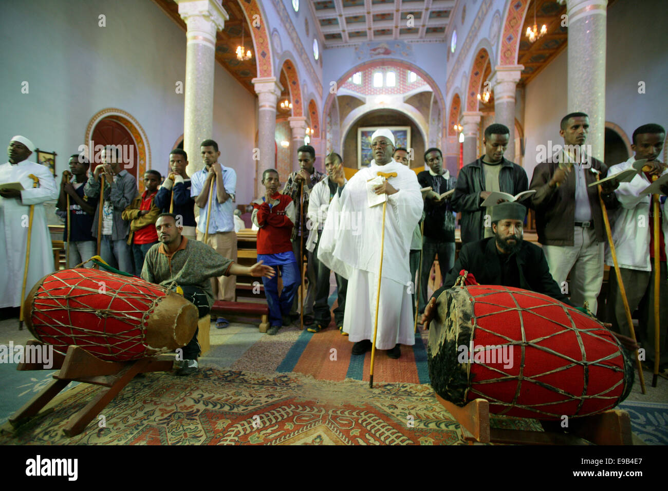 Priests with sticks sing during a vigil in the orthodox rite in the catholic Cathedral of the Holy Saviour, Adigrat, - Stock Image