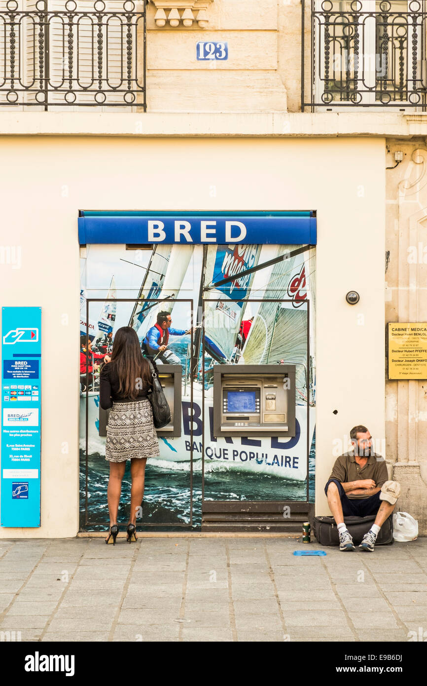 young woman withdrawing money from a cash dispenser, to the right a middle aged man is begging for money - Stock Image
