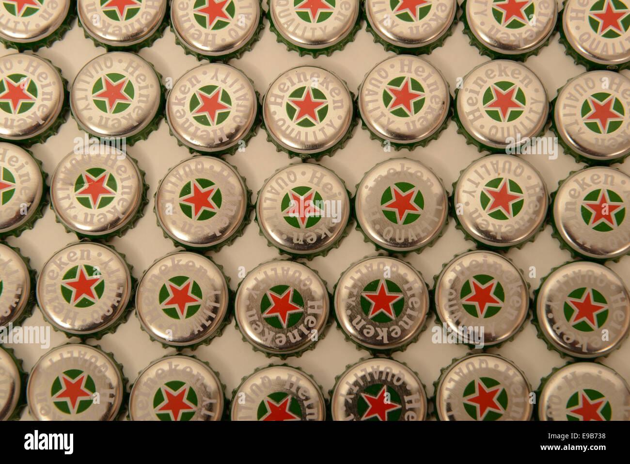 Rows of Heineken bottle caps against a white background - Stock Image