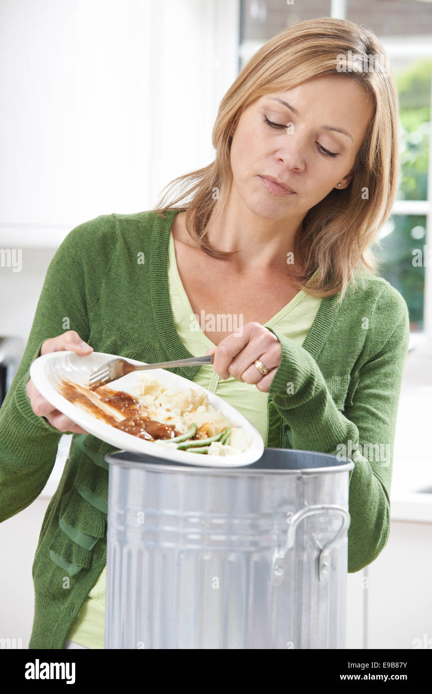 Woman Scraping Food Leftovers Into Garbage Bin - Stock Image