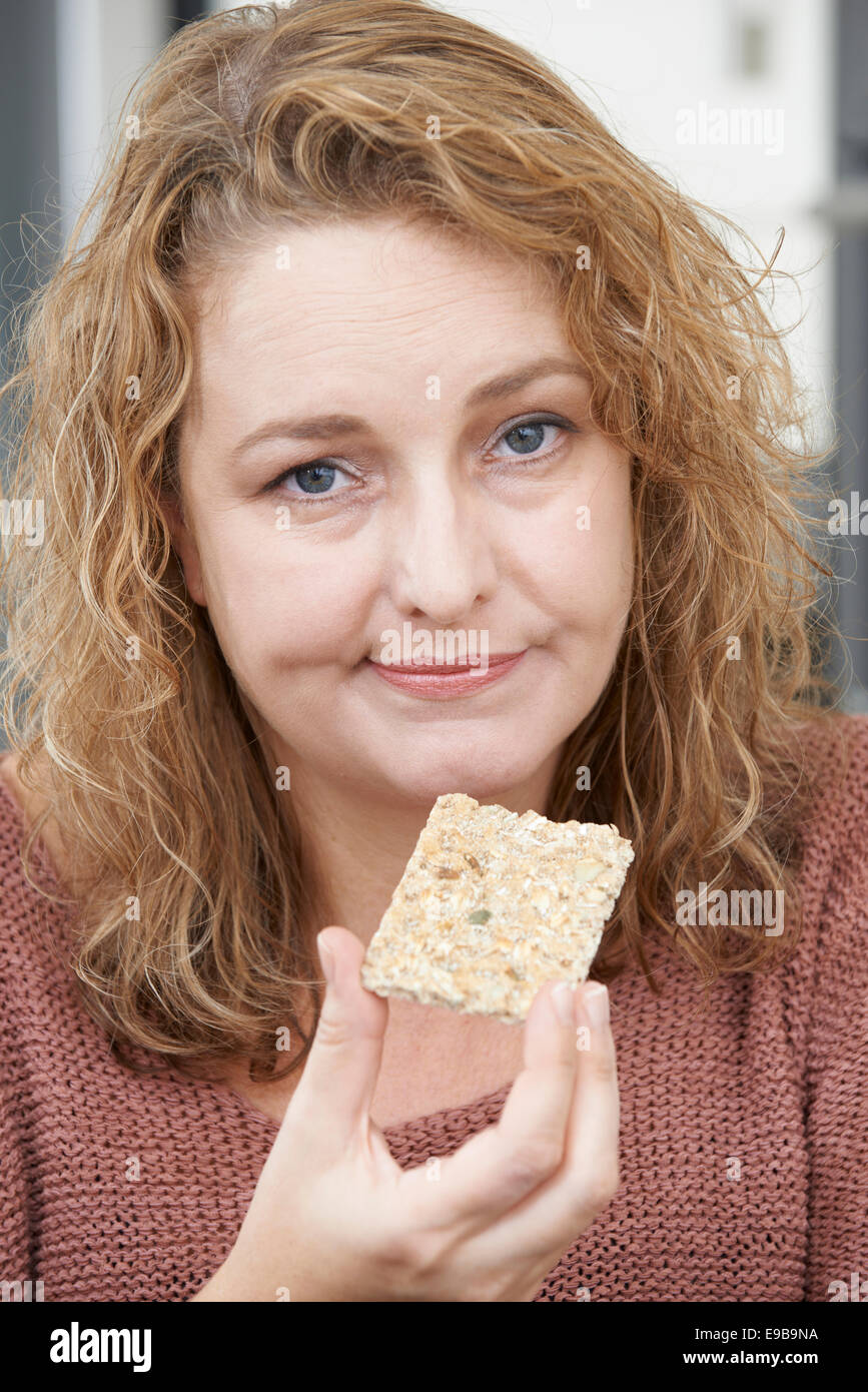 Bored Woman On Diet Eating Crispbread At Home - Stock Image