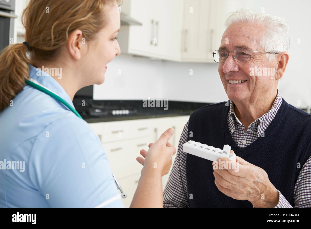 Nurse Helping Senior Man With Medication - Stock Image