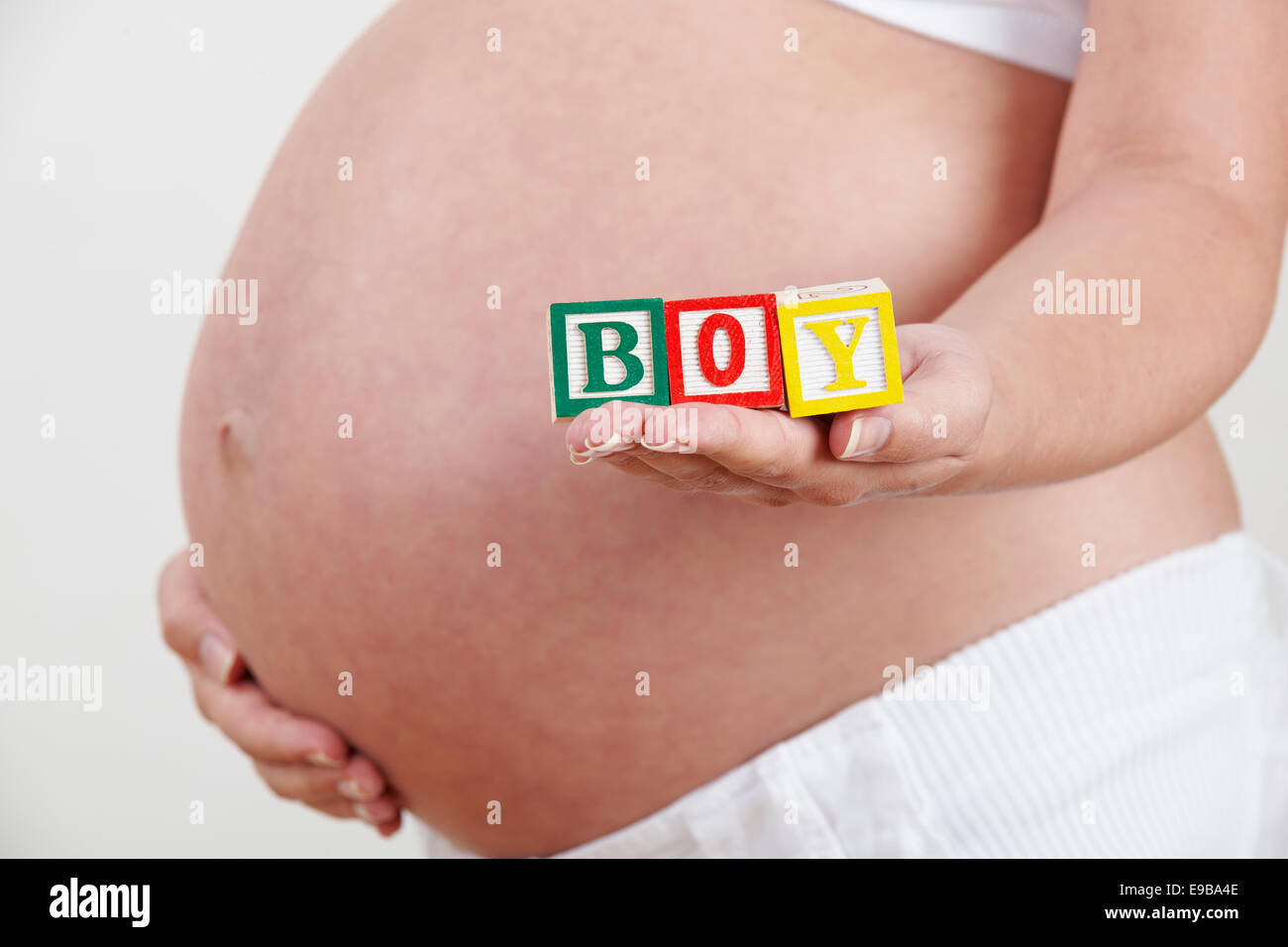 Pregnant Woman Holding Wooden Blocks Spelling Boy - Stock Image