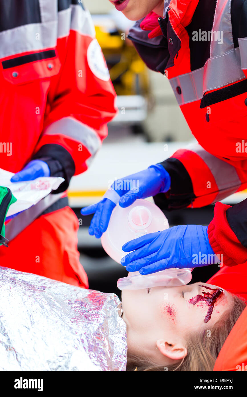Emergency doctor and nurse or ambulance team giving oxygen to accident victim - Stock Image