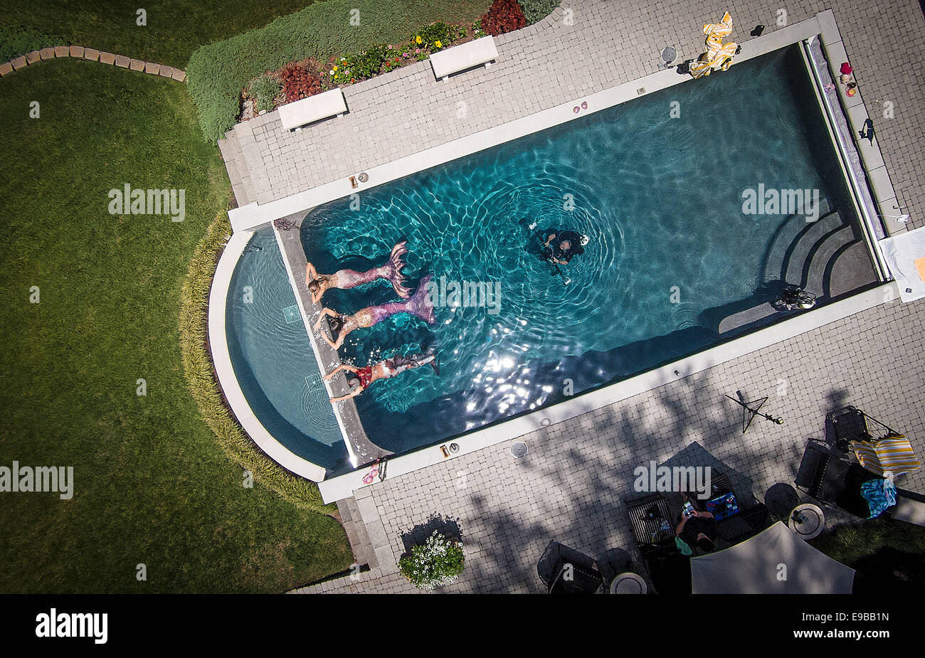 Aerial drone photo of three mermaids being photographed in a pool in Virginia Beach, Virginia. - Stock Image