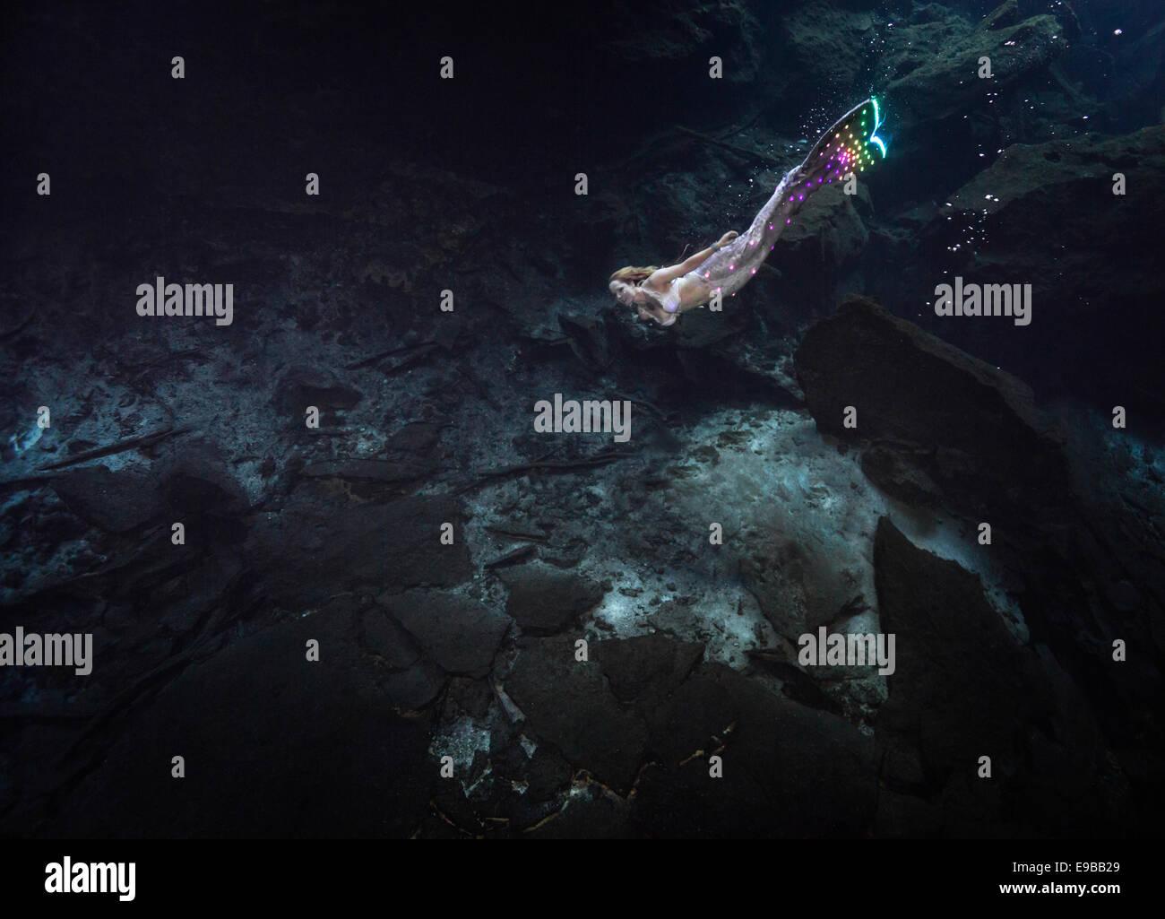 Mermaid with a glowing fluke swimming through the waters of Yucatan Peninsula, KuKulKan Cenote, QRoo, Mexico - Stock Image