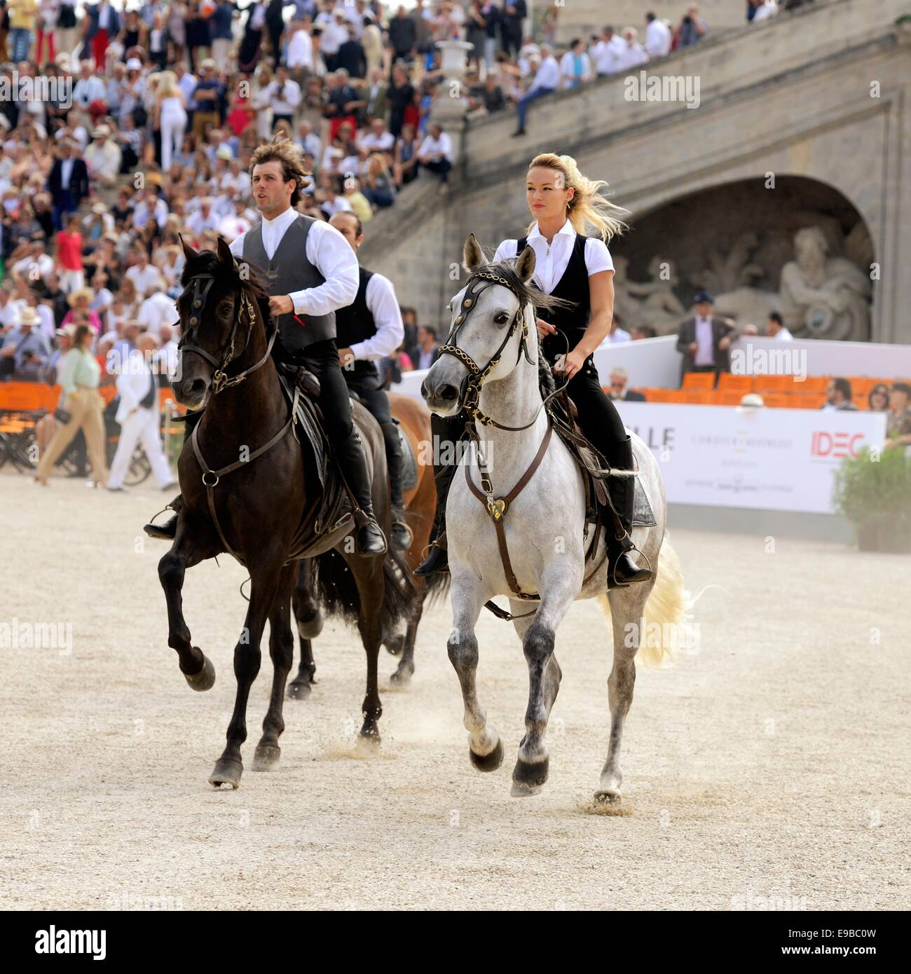 An equestrian team canter into an arena to give a display of stunt riding and horsemanship - Stock Image