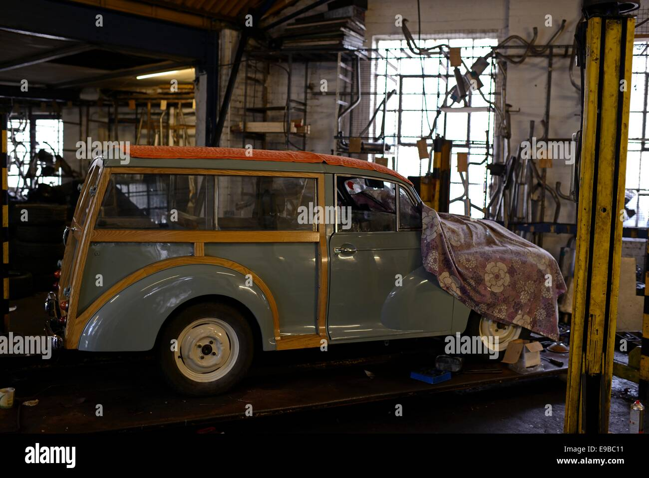 A Morris Minor Traveller Stands On Ramp With Blanket Over Its Bonnet In