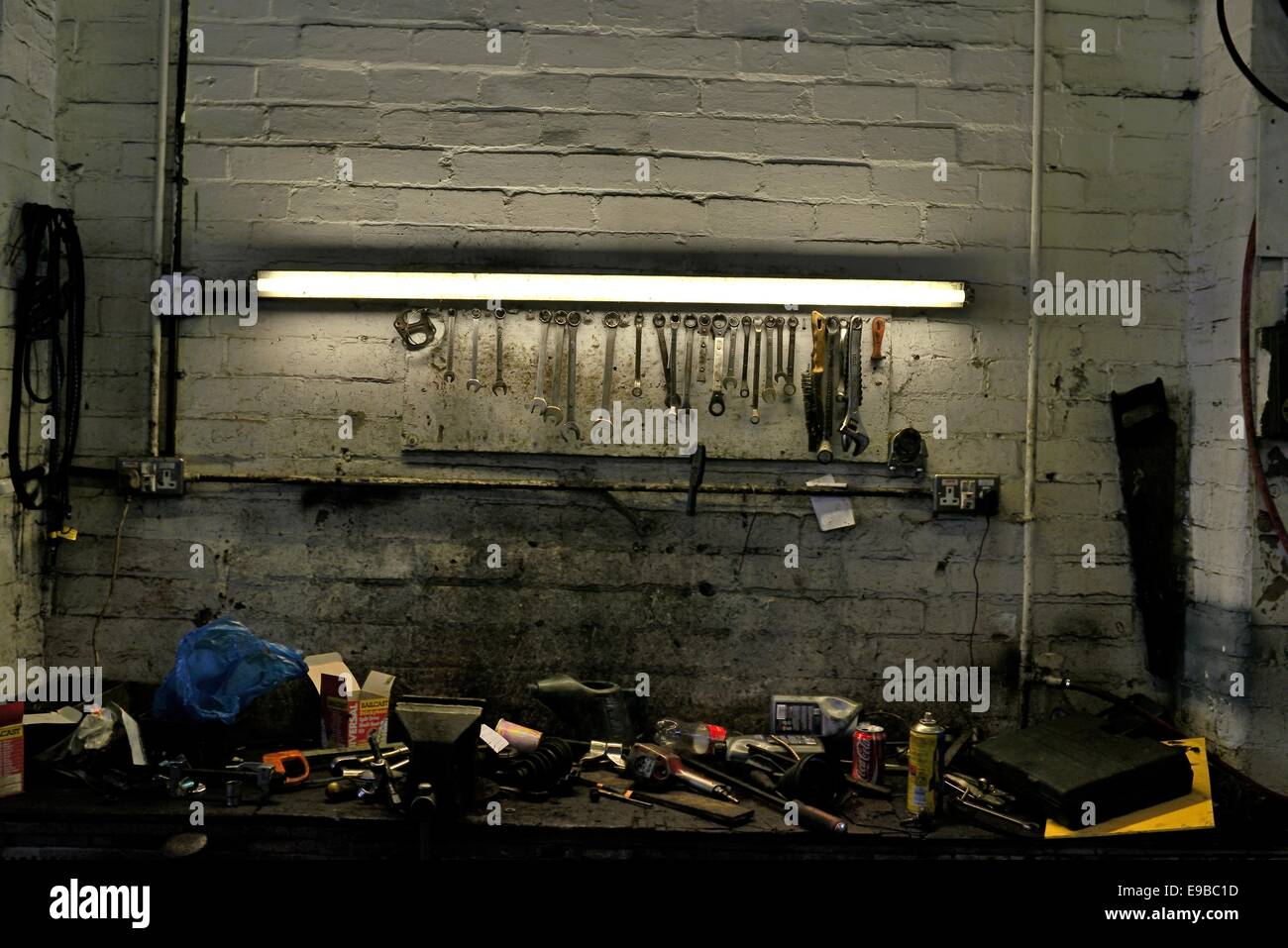 A fluorescent strip light illuminates spanners on a rack and scattered tools on a workbench - Stock Image