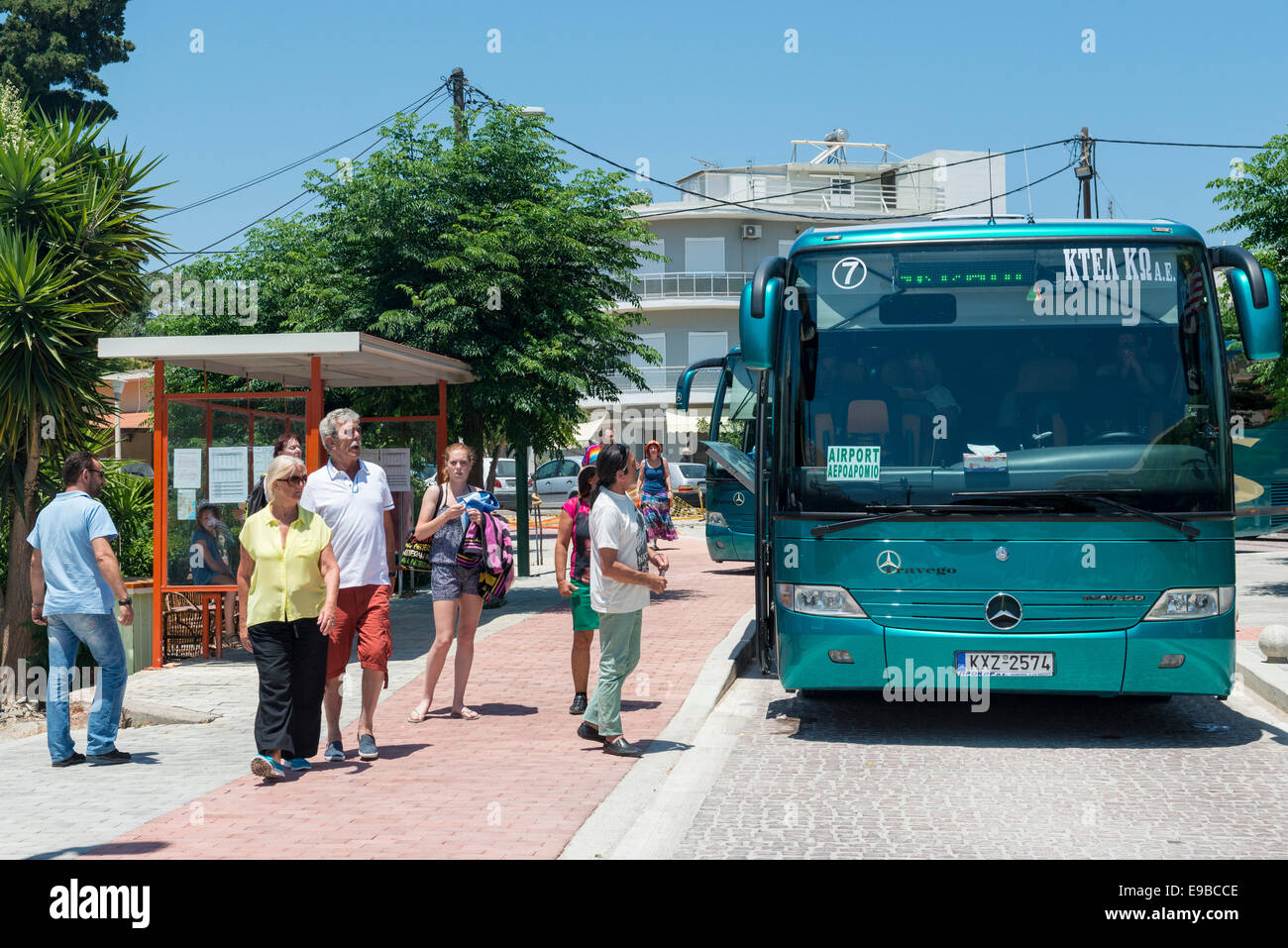 Passengers enter a bus at a bus stop in the town of Kos, island of Kos, Greece Stock Photo