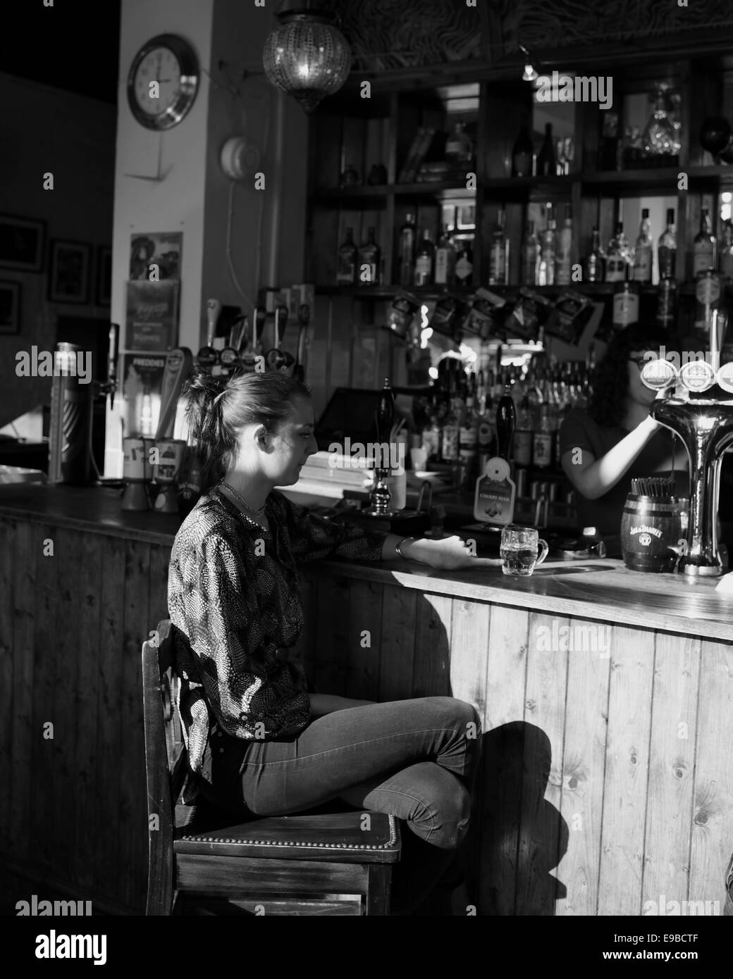 Young woman sitting at a bar, musing over her half pint of beer - Stock Image