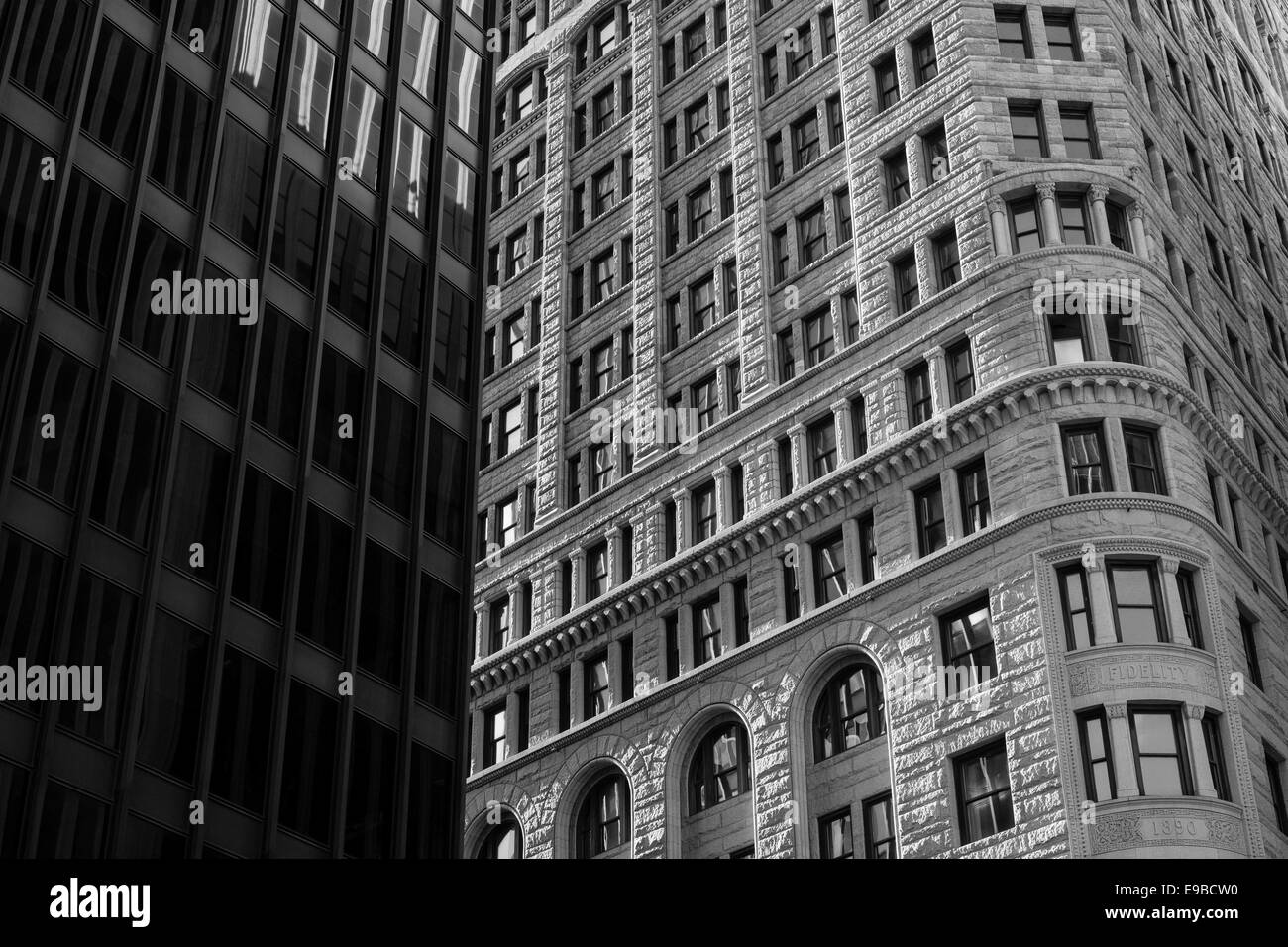 Old and modern buildings juxtaposed on a street in the business district of Baltimore. - Stock Image