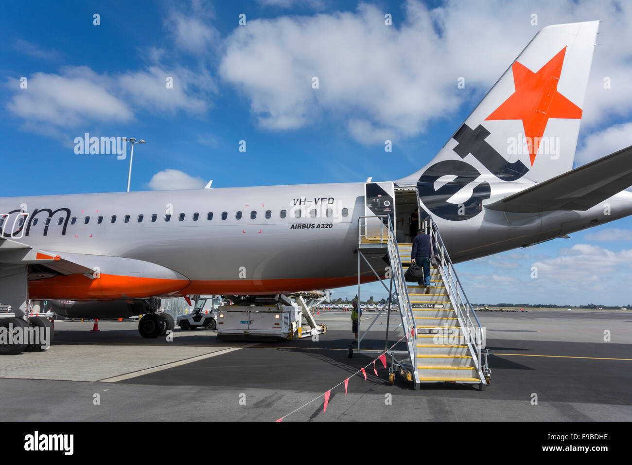 Jetstar A320 at Christchurch Airport. Single passenger boarding a Jetstar plane using a boarding ramp boarding stairs - Stock Image