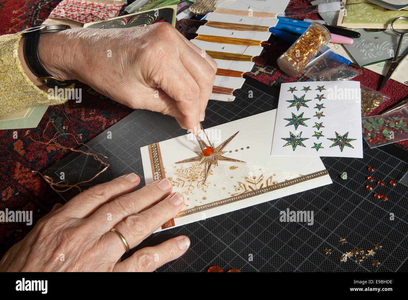 Hands of a woman crafting and scrap-booking christmas cards - Stock Image