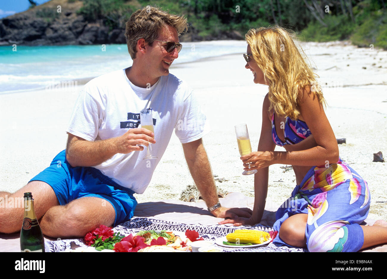 Honeymooners share a pre-lunch toast on their own private beach at Turtle Island, Fiji. - Stock Image