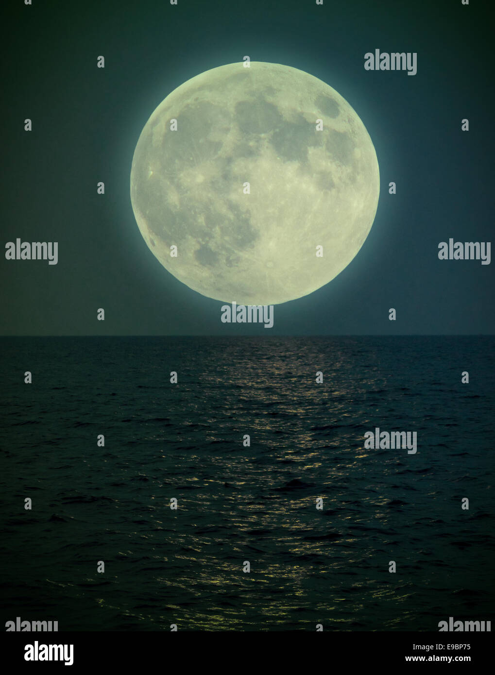 Halloween full super moon under the see getting the light on water - Stock Image