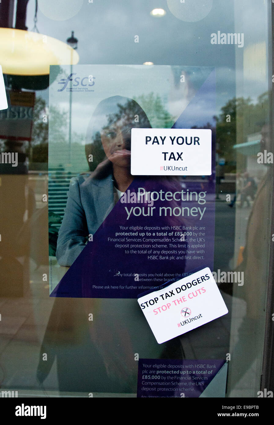 Protesters put UK Uncut stickers on shops they feel are dodging tax - Stock Image