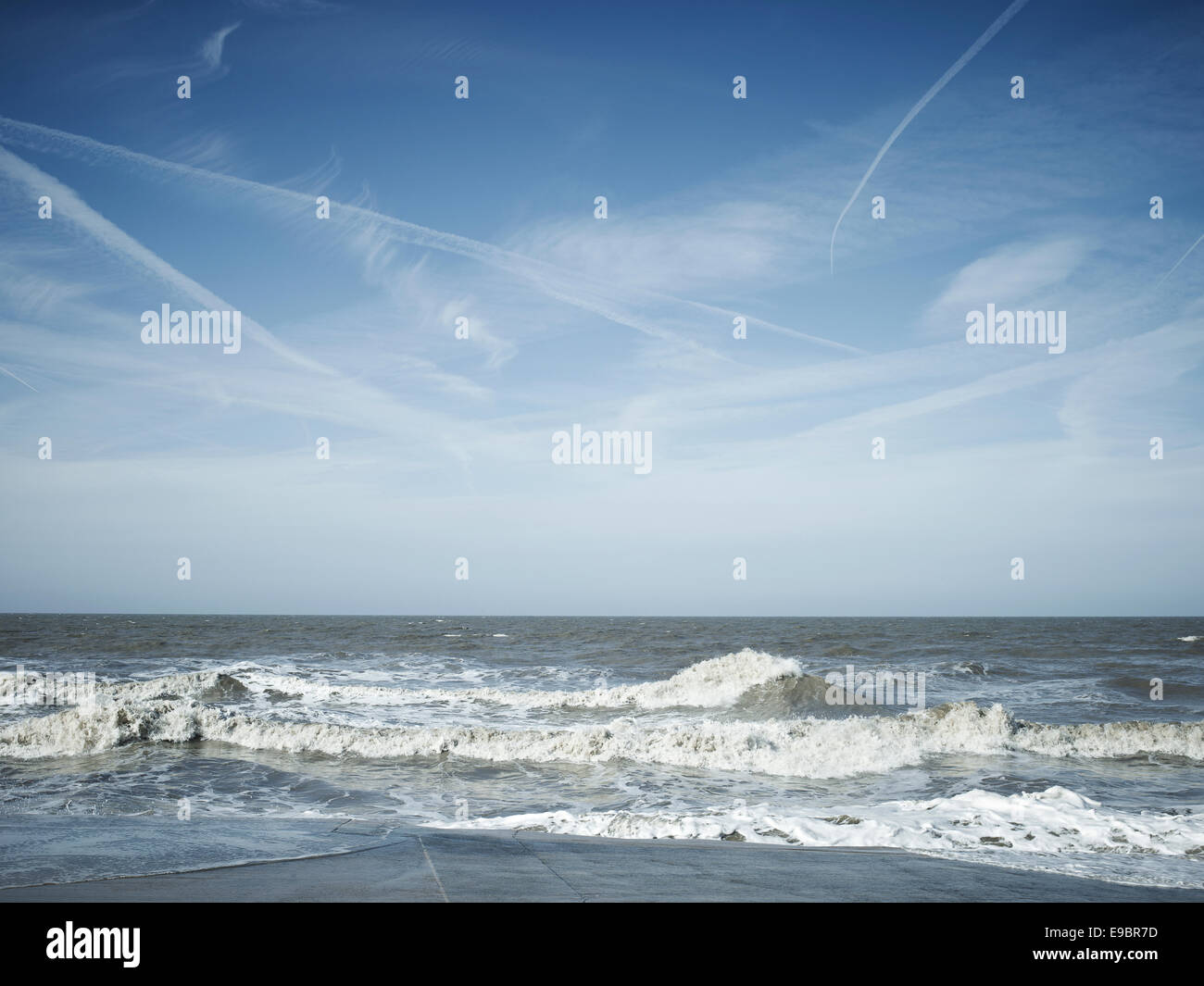 sea scape with waves and jet trails in the blue sky Blackpool seafront on the Fylde coast north west england. - Stock Image
