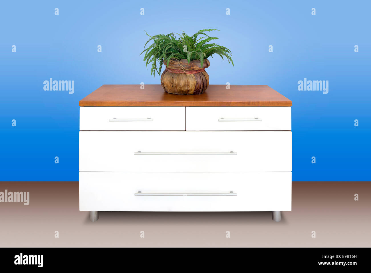 Modern white wooden chest of drawers, blue wall background - Stock Image