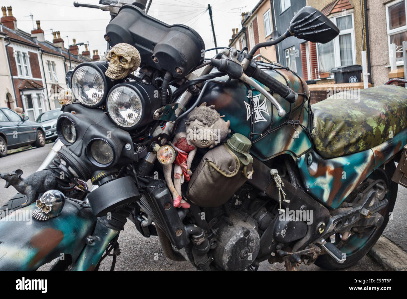 A motorcycle decorated for Halloween with skulls, skeletons, rats, gasmasks and even a Betty Boop doll - Stock Image