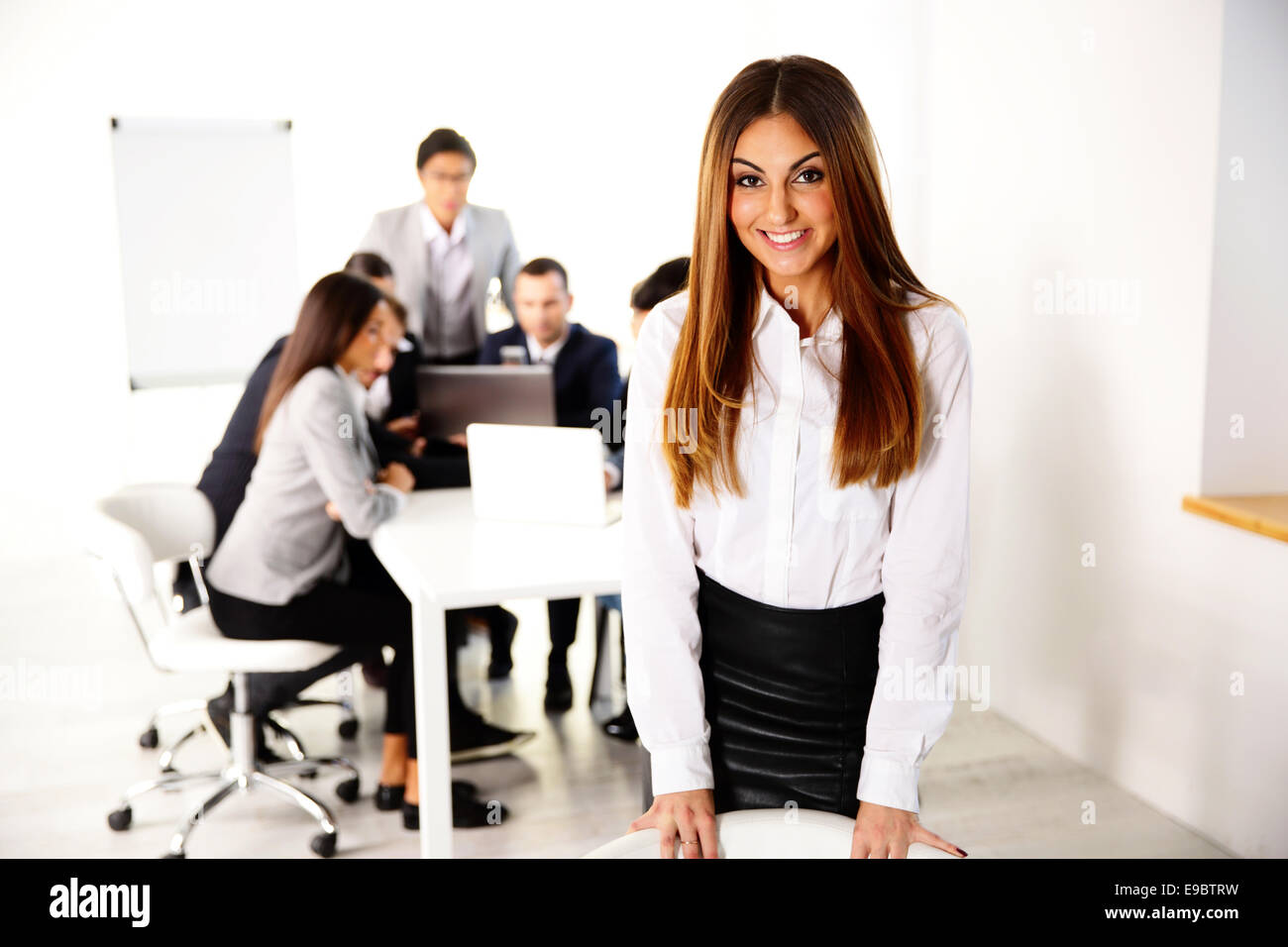 Portrait of a happy businesswoman in front of business meeting - Stock Image
