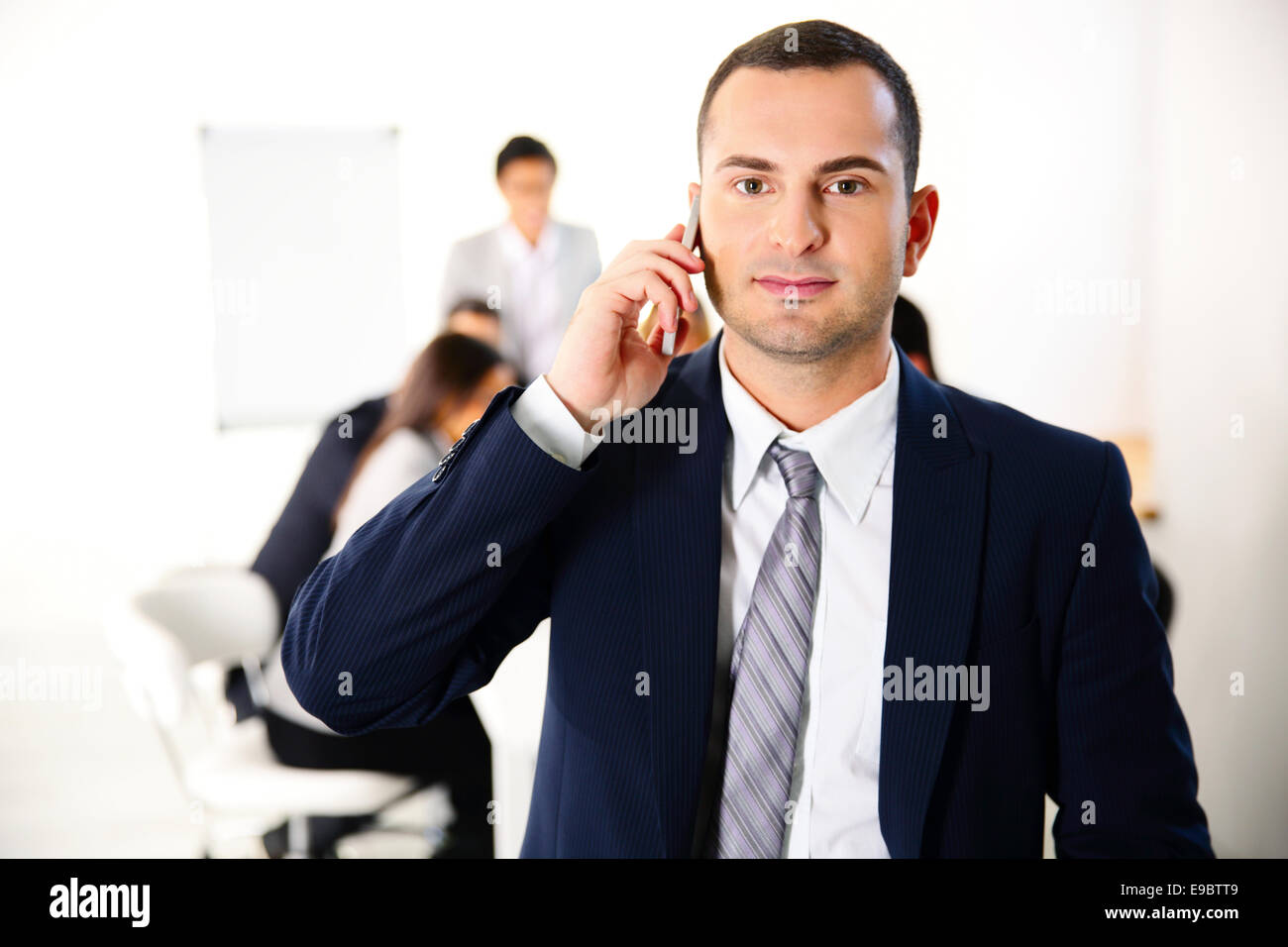 Businessman talking on the smartphone in front of business meeting - Stock Image