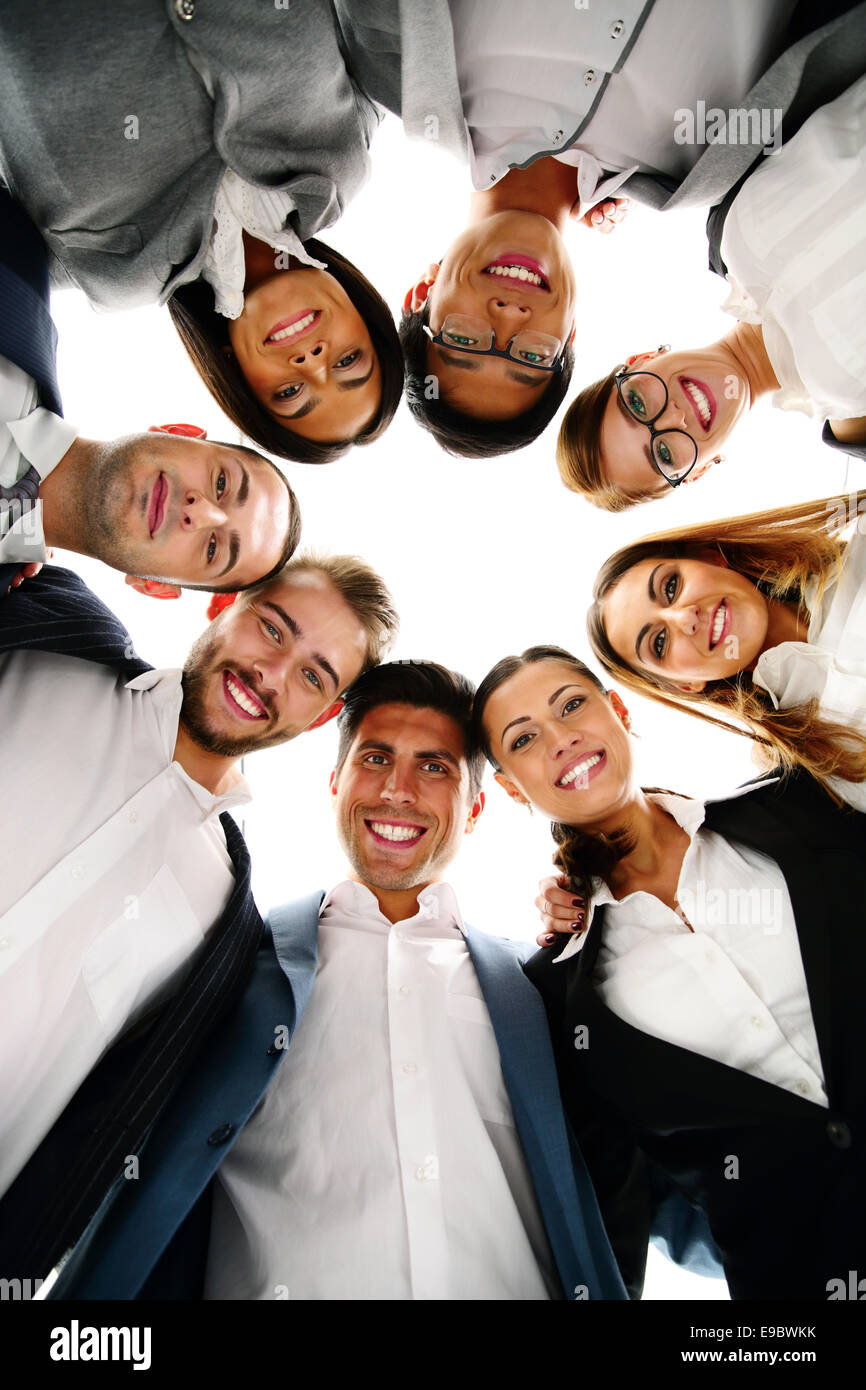 Group of business people in a circle looking down - Stock Image