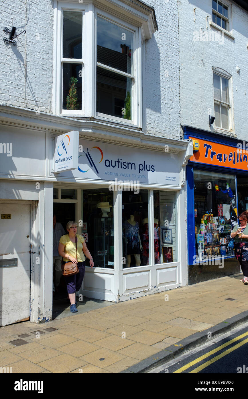 A woman leaves the 'Autism Plus' charity shop in central York, UK. - Stock Image