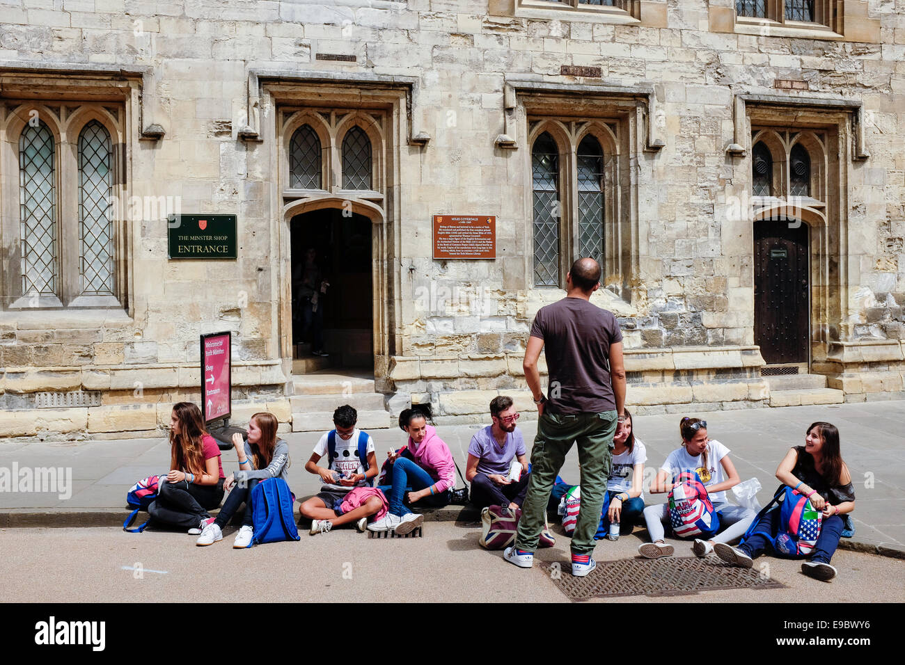 A small group of teenagers on a school visit to the York Minster wait on the pavement sidewalk outside the shop. - Stock Image