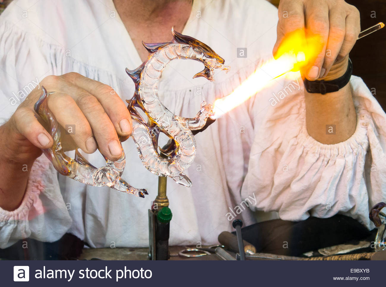 A glass-blower creating  a dragon of glass - Stock Image