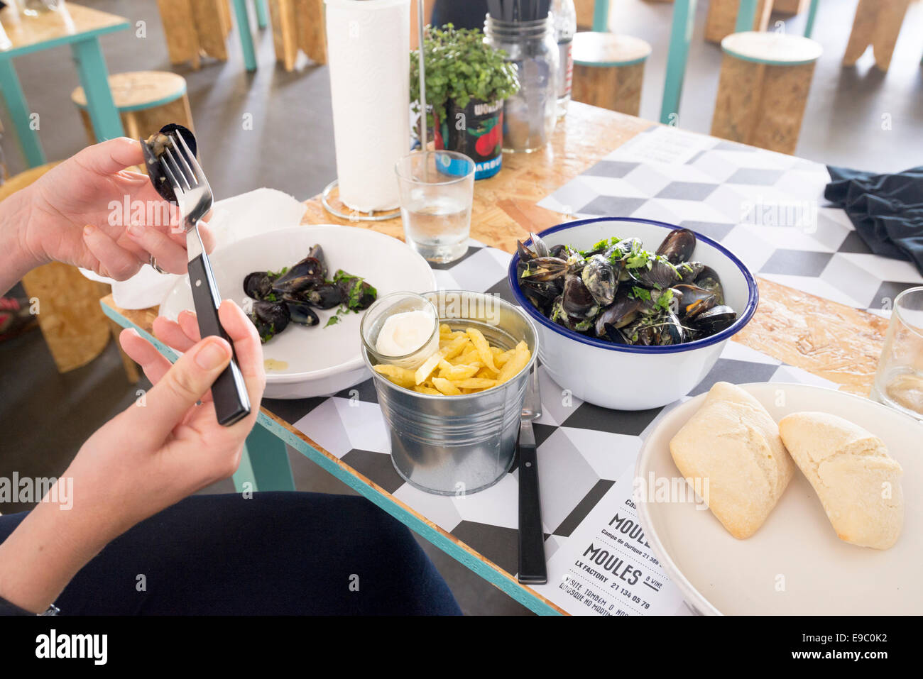 women eating mussles and bread at Moules & wine resturant in LX market, Lisbon, Portugal - Stock Image