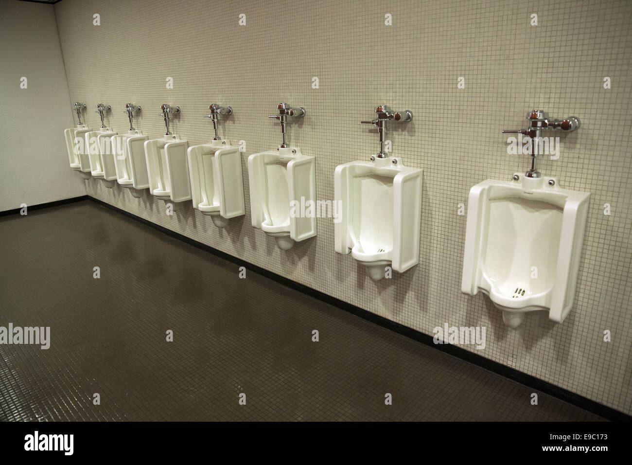 A Long Line Of Urinals In A Menu0027s Bathroom In A Manhattan Office Building.
